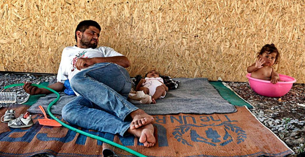 Mies ja lapset ovat pakolaisleirillä Kreikassa.