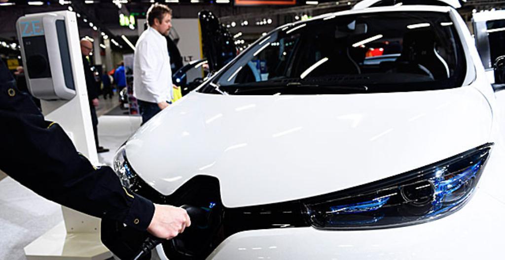 Kuljettaja laittaa sähköauton akun lataukseen.