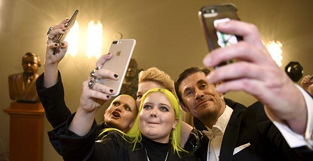 Poplaulaja Alma ja hänen siskonsa Anna (vasemmalla) ottavat selfieitä Linnan juhlilla. Heidän seurassaan on näyttelijä Tommi Korpela (oikealla).