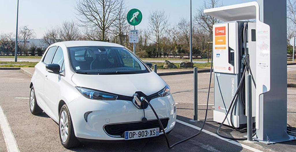 Kuvassa sähköauto on latauksessa latausasemalla.