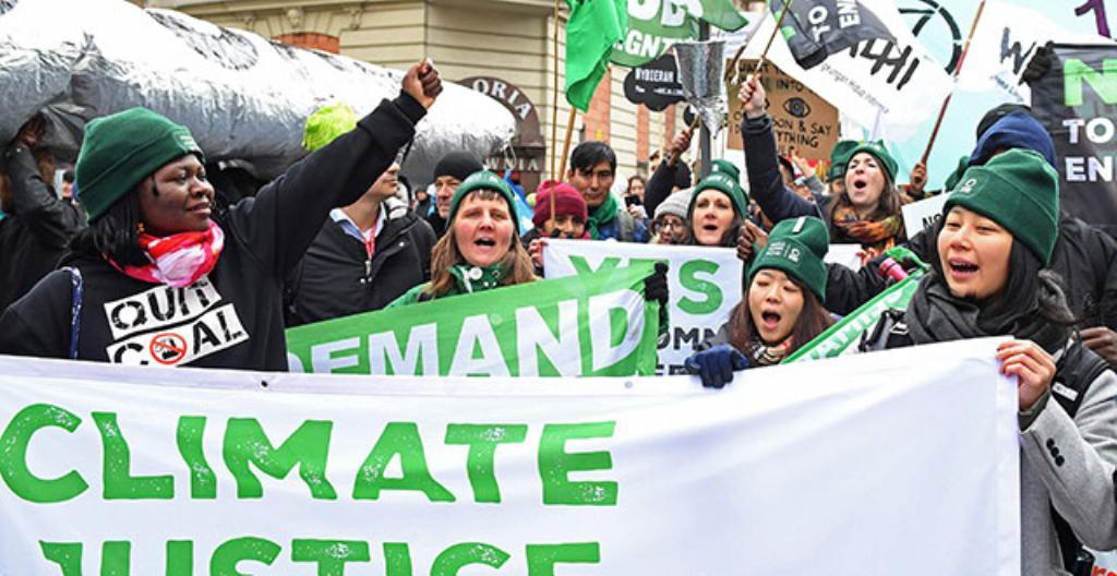 Mielenosoittajat vastustavat ilmastonmuutosta.