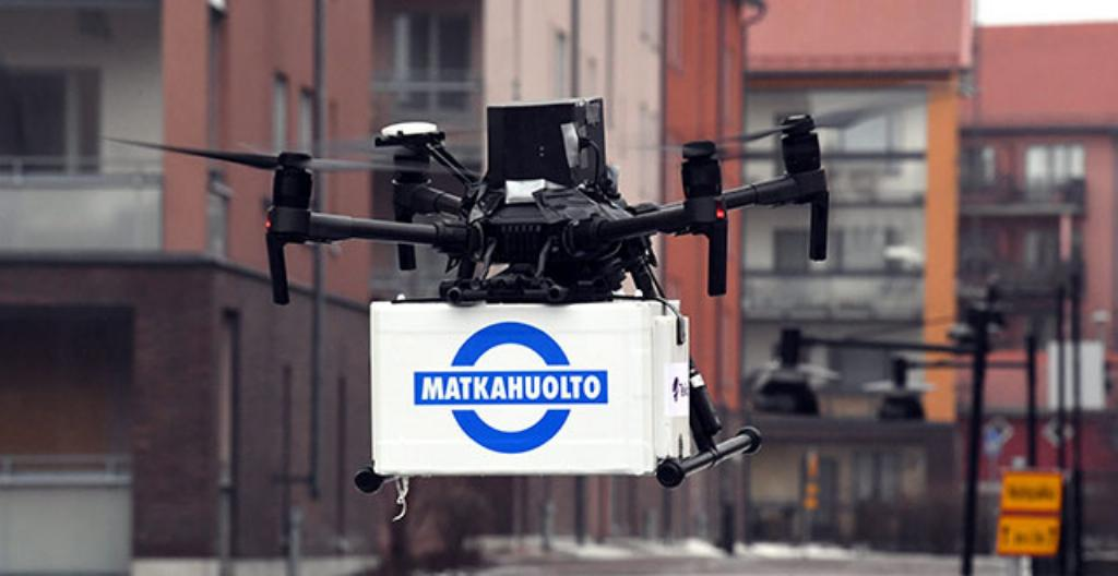Drooni eli robottilennokki kuljettaa Matkahuollon pakettia ilmassa.