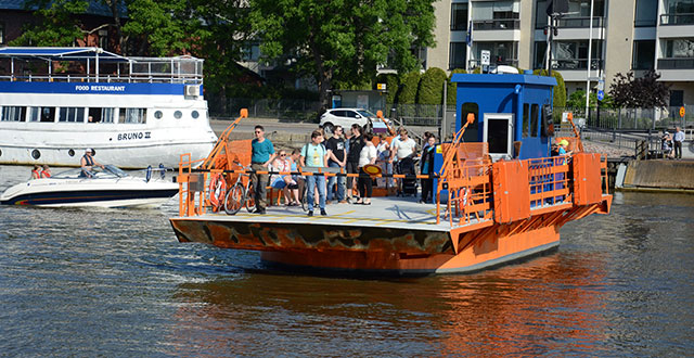 Kaupunkilautta Föri kuljettaa matkustajia Aurajoessa. Lautta on oranssi.