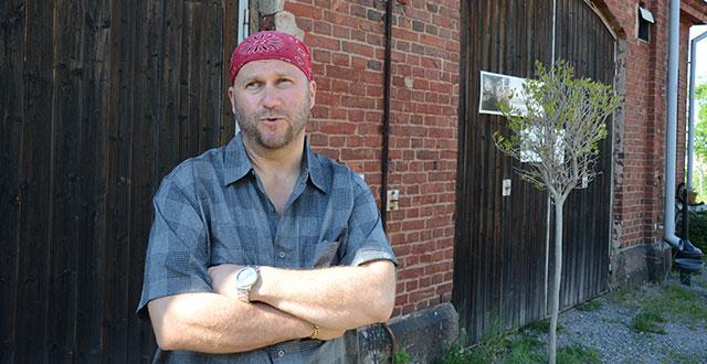 Heikki Sankari seisoo punatiilisen talon edessä. Hänellä on ruudullinen paita, punainen huivi päässä ja vähän partaa.