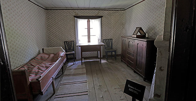 Tytön makuuhuoneessa on sänky, tuoleja ja lipasto.