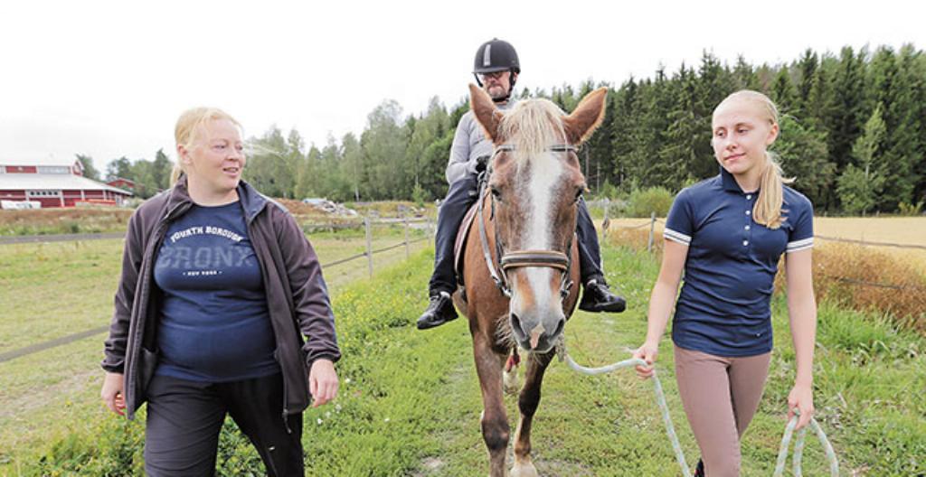 Johan Blomberg ratsastaa Megan-hevosella. Mukana ovat myös ohjaaja Merja Miettinen (vasemmalla) ja Saaga Sundström (oikealla).