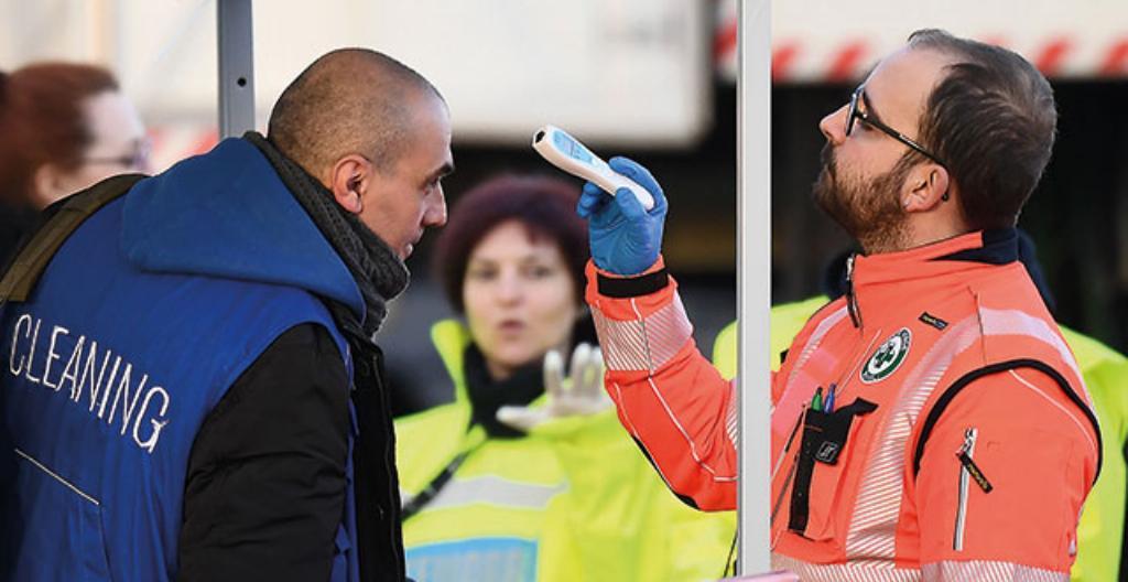 Kuvassa sairaanhoitaja tarkistaa, onko siistijällä kuumetta ja ehkä koronatartuntaa. Kuva on otettu Milanossa Italiassa ennen jalkapallo-ottelun alkua.