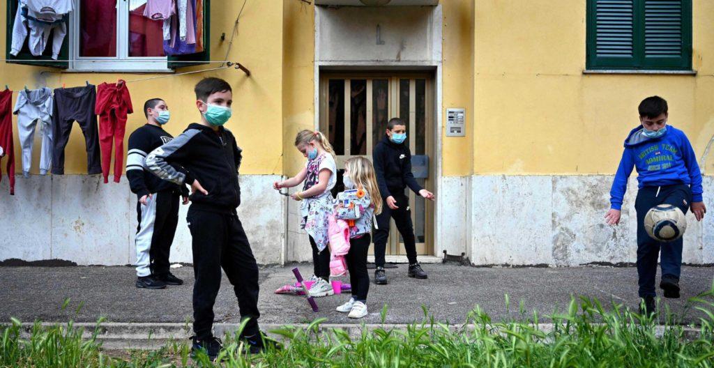 Kuvassa lapset leikkivät pihalla San Basilion kaupunginosassa Roomassa Italiassa. Lapset käyttävät hengityssuojaimia