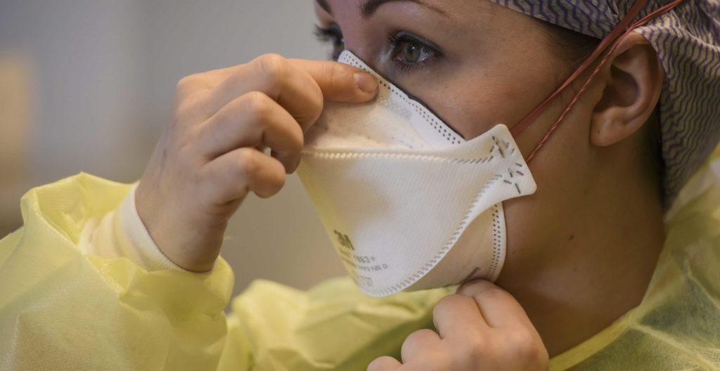 Kuvassa sairaanhoitaja Pamela Eriksson asettaa hengityssuojainta kasvoilleen.