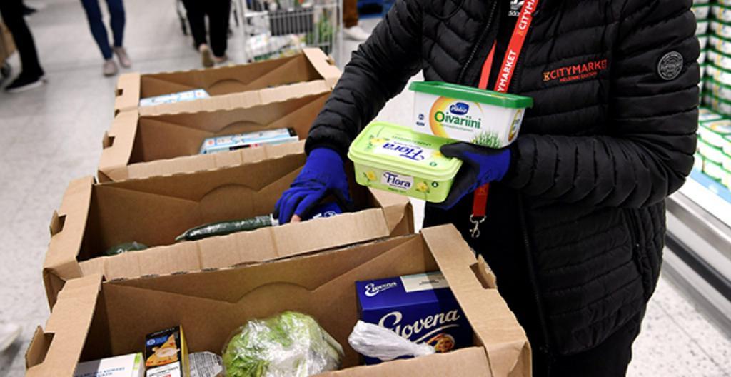 Kaupan työntekijät pakkaavat ruokaostoksia, jotka asiakas on tilannut verkkokaupasta.