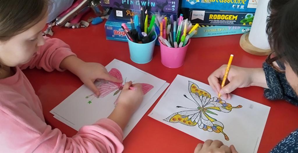 Kuvassa lapsi ja aikuinen värittävät kuvia.
