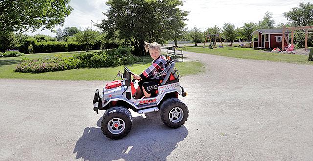 Tiitus Stenberg ajaa pienellä sähköautolla.
