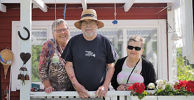 Arja-Leena, Kalevi ja Aija seisovat punaisen siirtolapuutarhamökin terassilla. He hymyilevät.