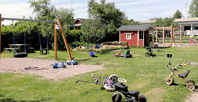 Lasten leikkipaikka, jossa on keinut, punainen leikkimökki ja kiipeilyteline. Nurmikolla on paljon leluja ja pieniä polkupyöriä.