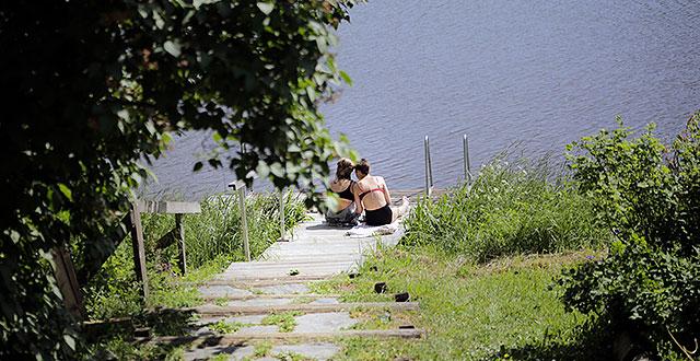 Leena ja Hertta istuvat laiturilla joen rannassa. Portaat johtavat joen rantaan.