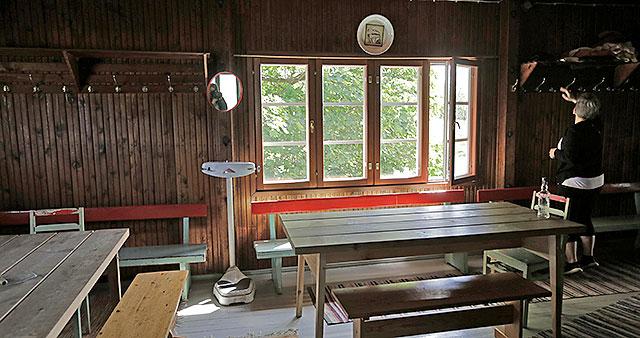 Saunan pukuhuoneessa on pöytiä, tuoleja ja naulakoita. Siellä on myös iso ikkuna. Nainen seisoo pukuhuoneessa.