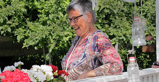 Arja-Leena nojaa terassin kaiteeseen. Hän nauraa. Taustalla näkyy omenapuita.