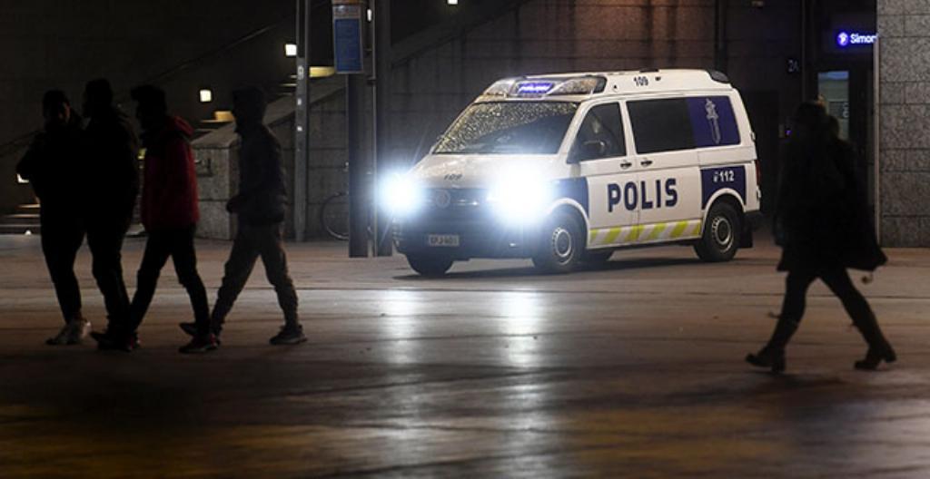 Jalankulkijoita ja poliisiauto Narinkkatorilla Helsingin keskustassa.