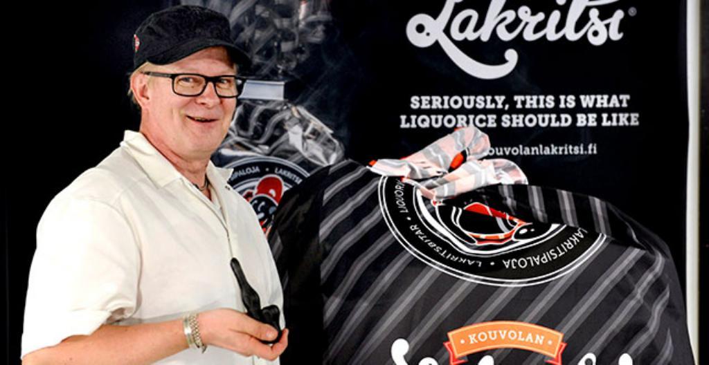 Timo Nisula on lakritsitehtailija Kouvolan Lakritsilla. Kuvassa Nisula pitää kädessä todella suurta lakritsipussia ja lakritsipiippua.